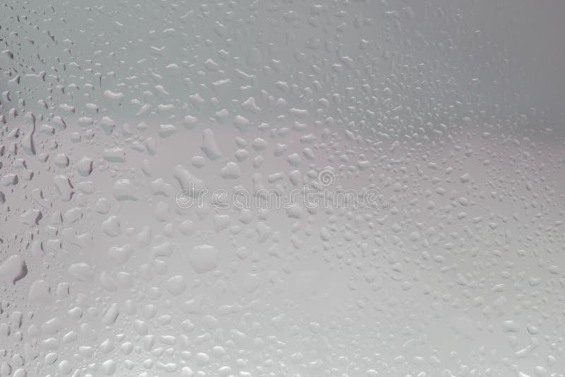 Tekstura od deszczu opuszcza przy okno przeciw domowi obraz stock