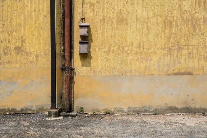 Tekstura stara żółta rocznik ściana przemysłowa fabryka z rdzewiejącym żelaznym elektrycznym kablem i słupem obraz stock
