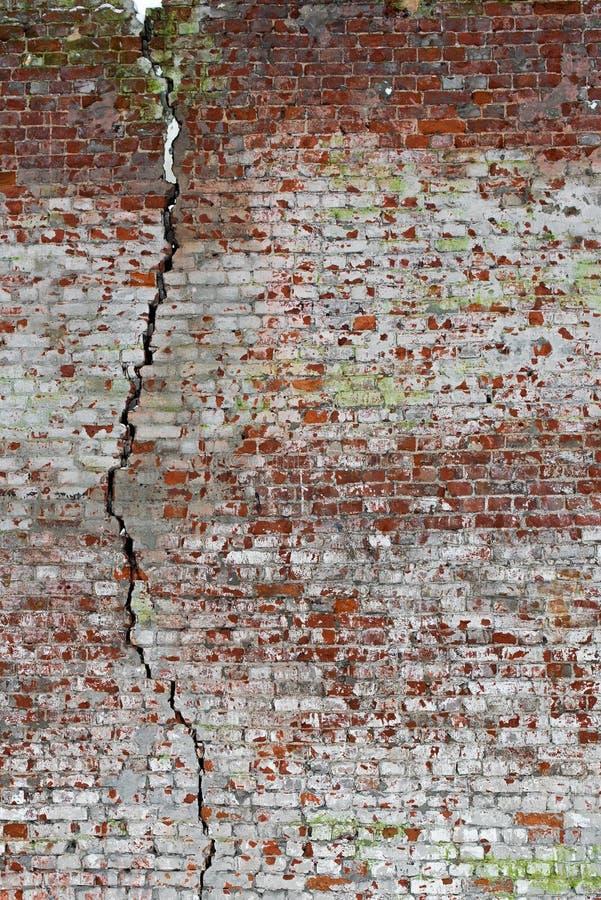 Tekstura stary uszkadzający czerwony ściana z cegieł z wielkim pęknięciem fotografia royalty free