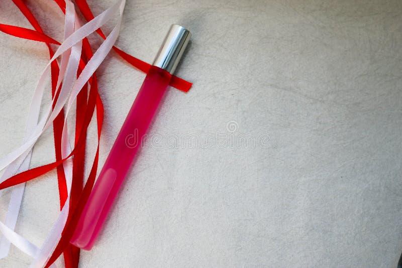 Tekstura z różowego matte pachnidła cienką długą cylindryczną butelką, cologne z czerwonymi i białymi pięknymi świątecznymi fabor zdjęcie stock