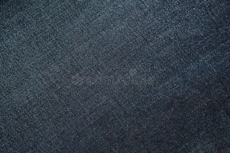 Tekstura zmrok - niebiescy dżinsy, tkaniny tło zdjęcia stock
