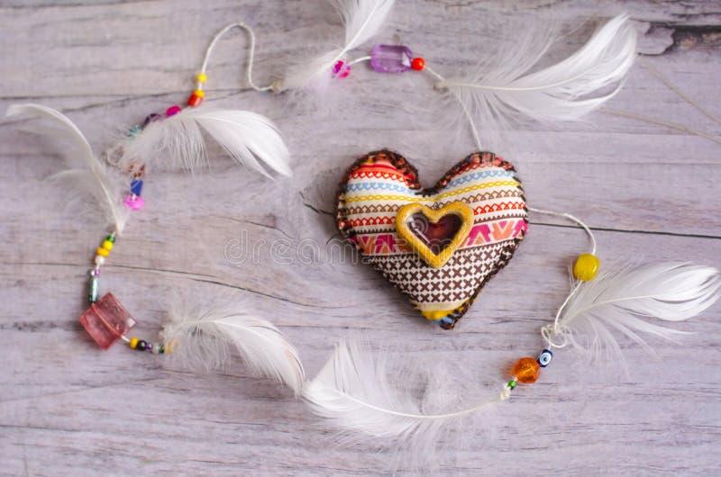 Tekstylny serce handmade z etnicznym ornamentem na szarawym starym starzejącym się tle dekoracyjny element biali piórka Ceramiczn zdjęcie royalty free