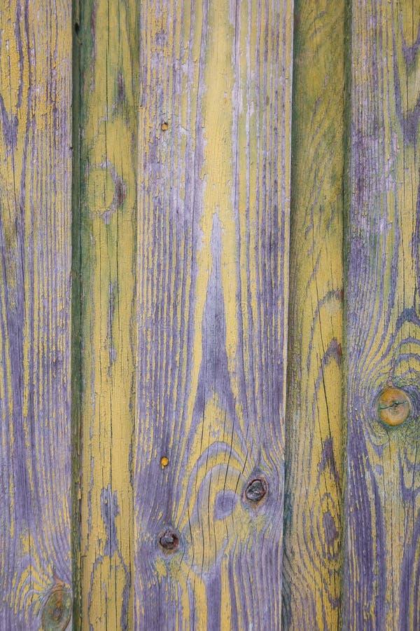 Tekturas-Bretterzaun mit Resten der purpurroten und gelben Farbe lizenzfreies stockbild