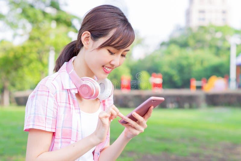 Teléfono asiático joven del uso de la mujer imagenes de archivo