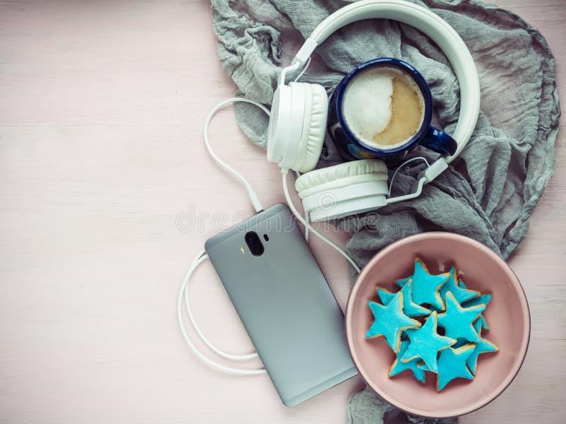 Teléfono, auriculares, una taza de capuchino fragante foto de archivo libre de regalías