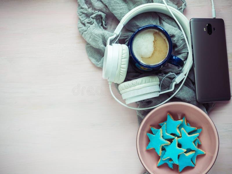 Teléfono, auriculares, una taza de capuchino fragante fotos de archivo libres de regalías