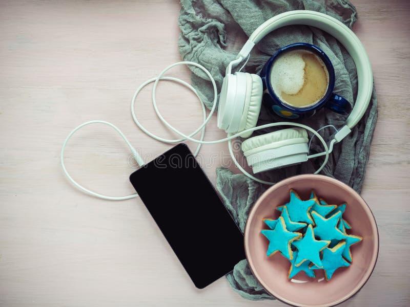 Teléfono, auriculares, una taza de capuchino fragante fotos de archivo