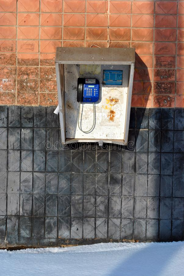 Teléfono azul público con la tabla de números de los servicios de emergencia y de número del operador dentro imagen de archivo libre de regalías