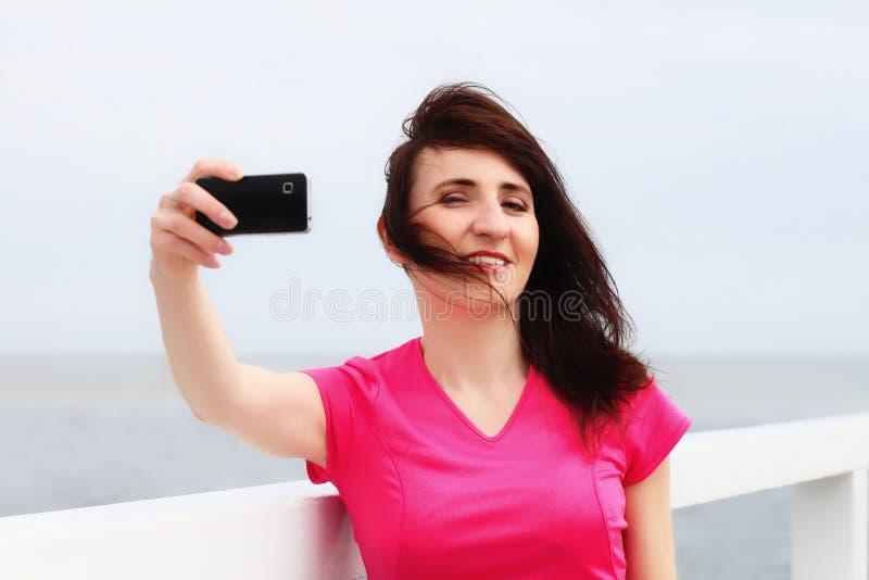 Teléfono bonito joven de la visualización de la demostración de la mujer imagen de archivo libre de regalías