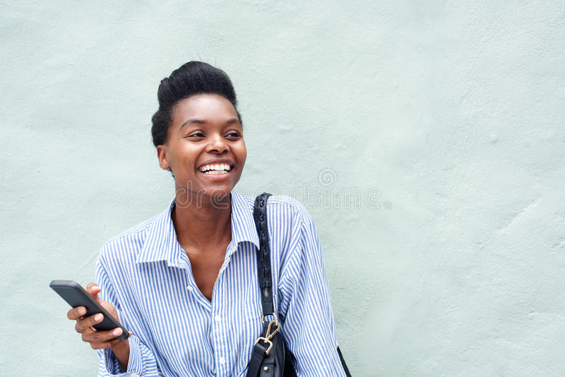 Teléfono celular alegre de tenencia de la mujer negra fotografía de archivo