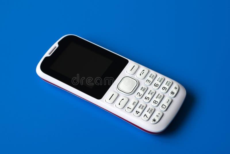 Teléfono celular blanco con los botones en fondo azul fotos de archivo