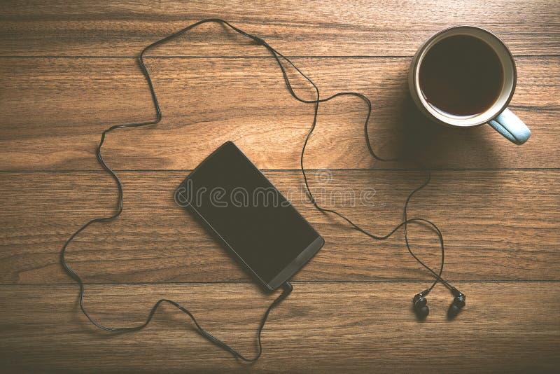Teléfono celular con los auriculares y el café en la madera fotografía de archivo libre de regalías
