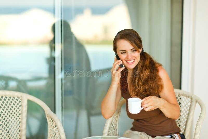 Teléfono celular de discurso de la muchacha feliz en la terraza fotografía de archivo libre de regalías