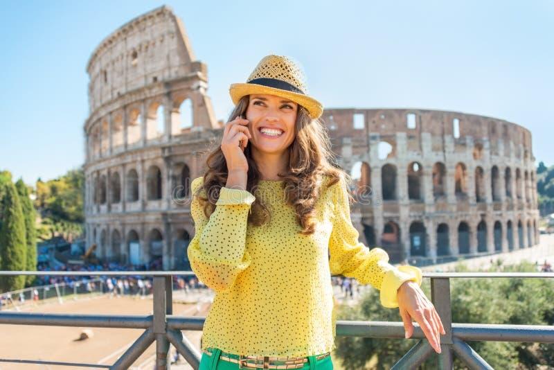 Teléfono celular de la mujer que habla delante del colosseum adentro imagen de archivo libre de regalías