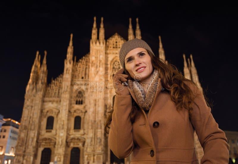 Teléfono celular de la mujer que habla joven cerca del Duomo por la tarde, Milán foto de archivo libre de regalías