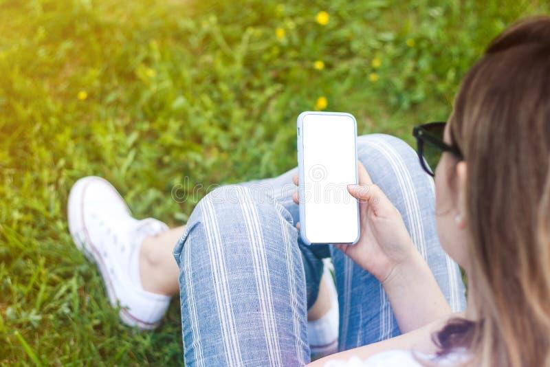 Teléfono celular de tenencia de la mujer con la pantalla en blanco en su mano Fondo de la hierba, rayos del sol fotos de archivo libres de regalías
