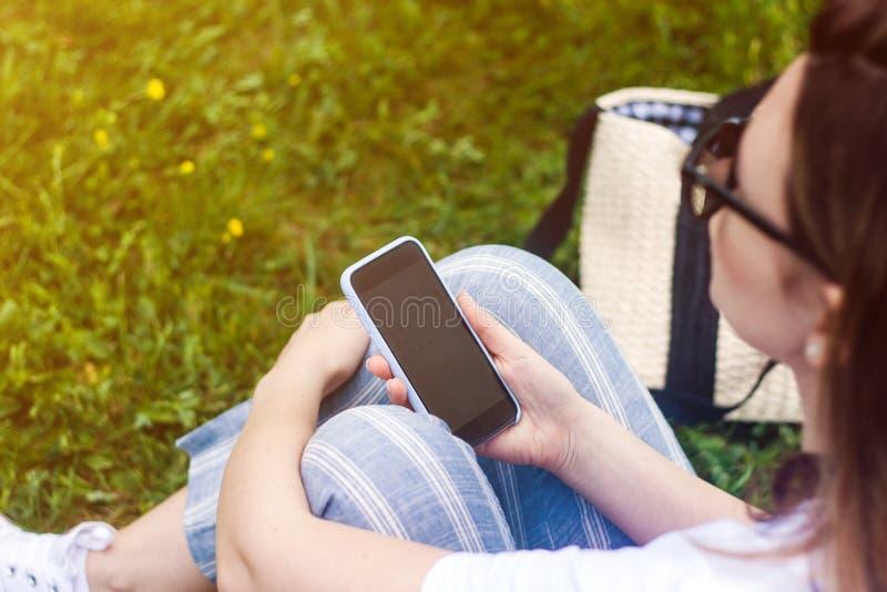 Teléfono celular de tenencia de la mujer con la pantalla oscura en su mano Fondo de la hierba, rayos del sol imagen de archivo