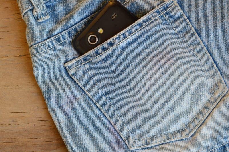 Teléfono celular en el bolsillo trasero de las bragas azules cortas de la mezclilla en el tablero de madera imagen de archivo libre de regalías