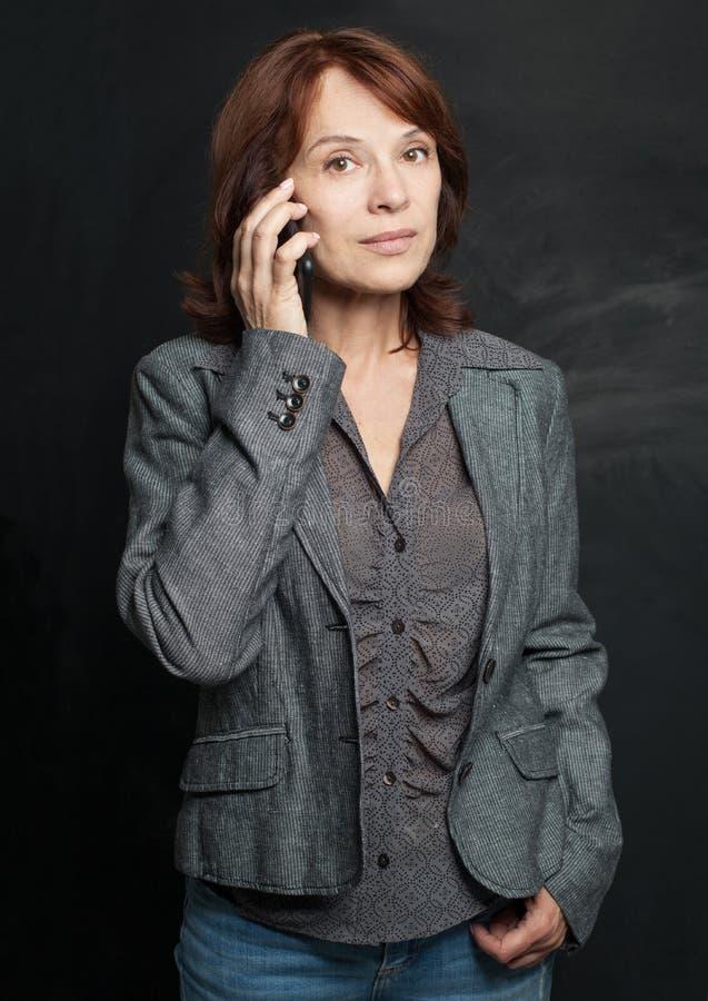 Teléfono celular hermoso de la mujer de negocios maduros fotografía de archivo