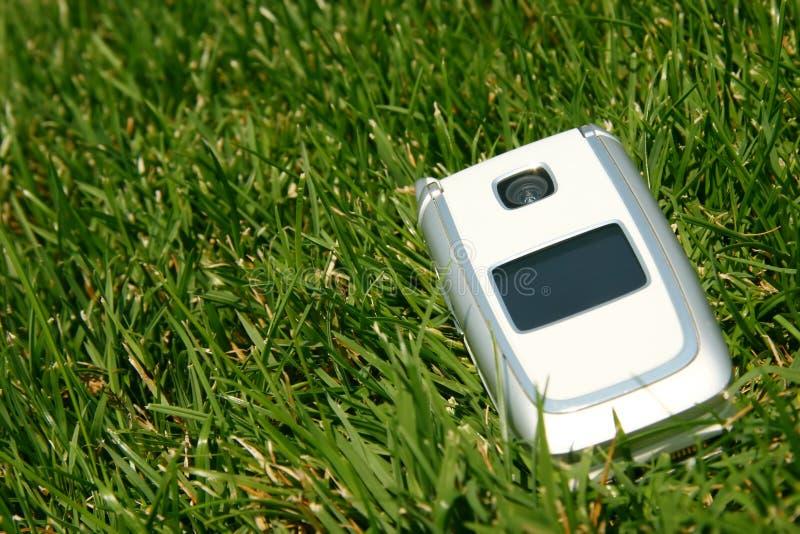 Teléfono celular móvil en hierba afuera foto de archivo
