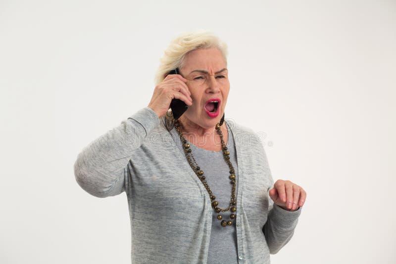 Teléfono celular mayor de tenencia de la mujer fotografía de archivo