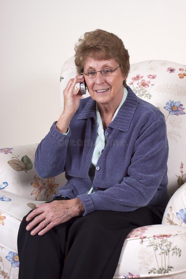 Teléfono celular mayor maduro de la charla de la sonrisa de la mujer foto de archivo libre de regalías
