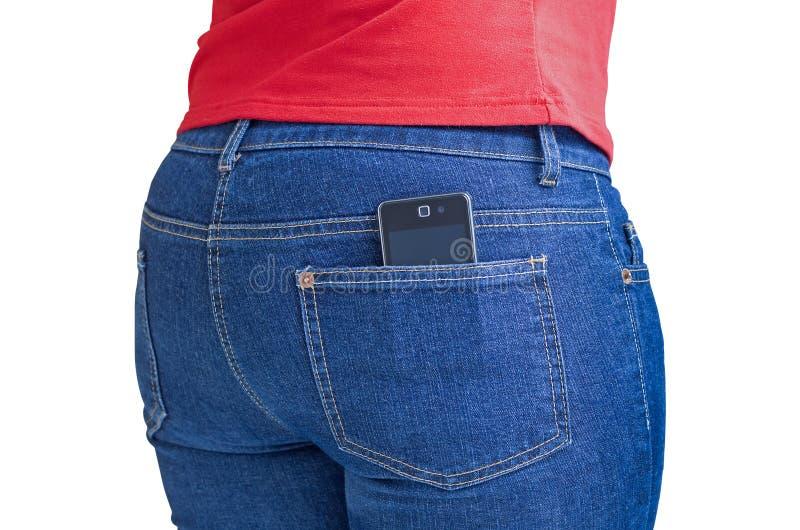 Teléfono celular moderno que se pega fuera de un bolsillo de los pantalones vaqueros imagenes de archivo