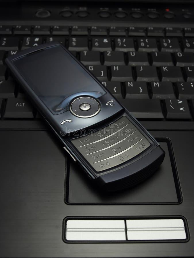 Teléfono celular negro en la computadora portátil imagen de archivo libre de regalías