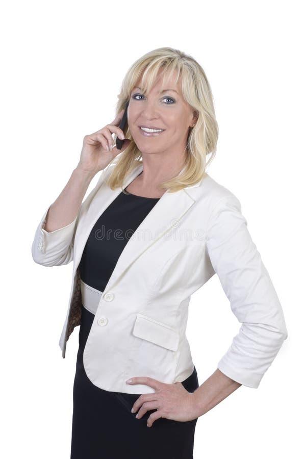 Teléfono celular sonriente del whith de la mujer de negocios maduros fotos de archivo libres de regalías