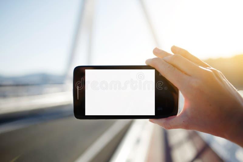 Teléfono celular turístico de tenencia de la mujer mientras que toma una fotografía del paisaje en viaje del verano foto de archivo libre de regalías