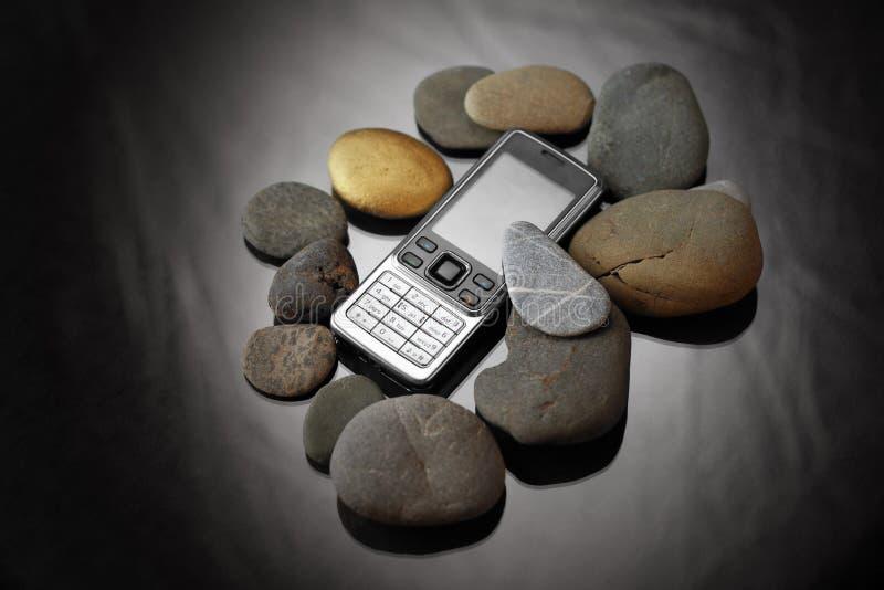 Teléfono celular y piedras fotografía de archivo