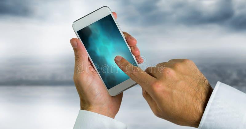 teléfono conmovedor de la mano con pendiente azul imagen de archivo