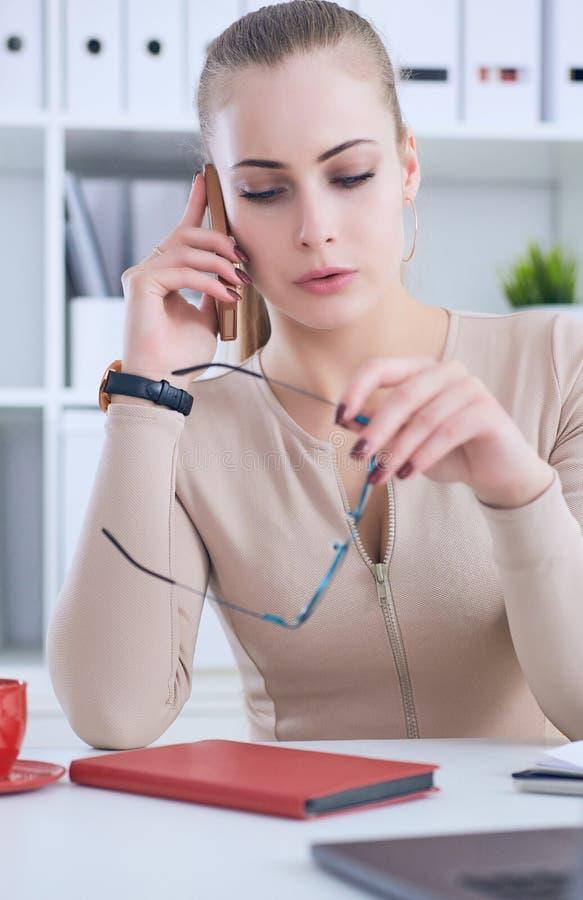 Teléfono de discurso de la empresaria joven hermosa mientras que usa el ordenador portátil y hace un cierto papeleo fotos de archivo