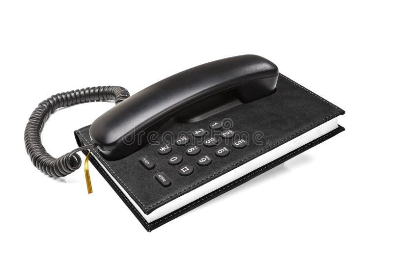 Teléfono de escritorio de la oficina vieja con la guía telefónica fotos de archivo