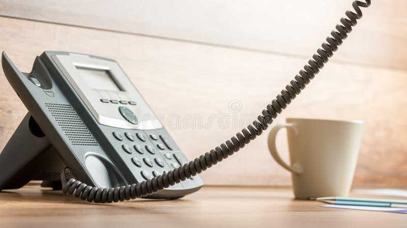 Teléfono de la línea horizonte de Blacka y taza de café en el escritorio de oficina foto de archivo