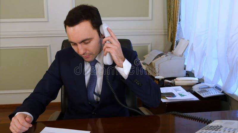Teléfono de la línea horizonte del hombre de negocios que habla hermoso que comprueba al equipo foto de archivo