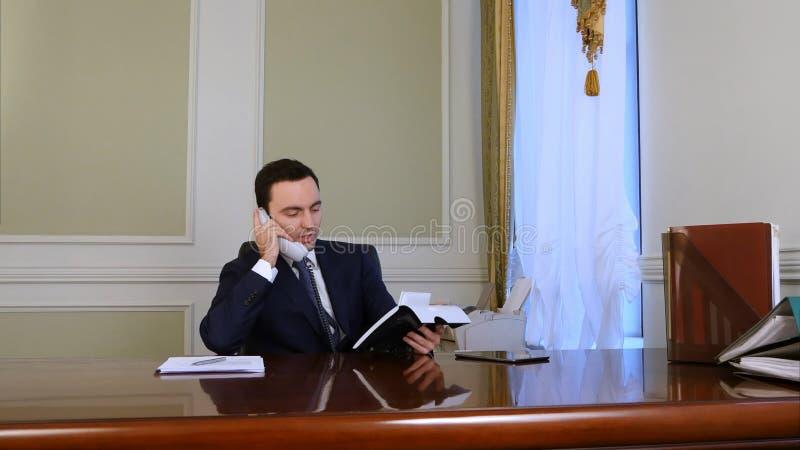 Teléfono de la línea horizonte del hombre de negocios que habla joven ocupado que tiene conversación de la sociedad en oficina foto de archivo libre de regalías