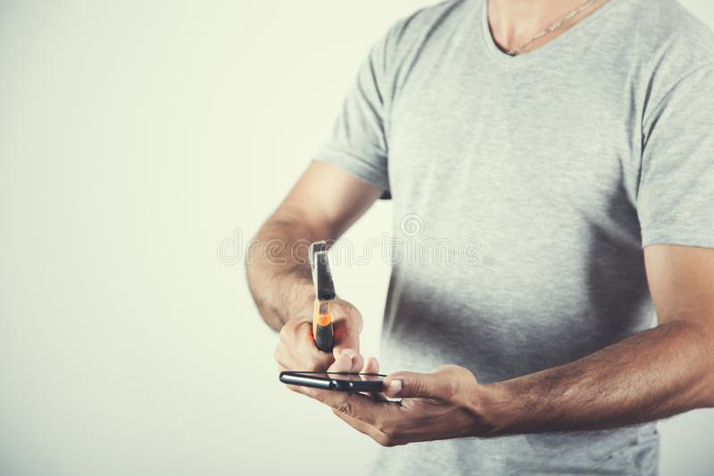 Teléfono de la mano del hombre con el martillo imágenes de archivo libres de regalías