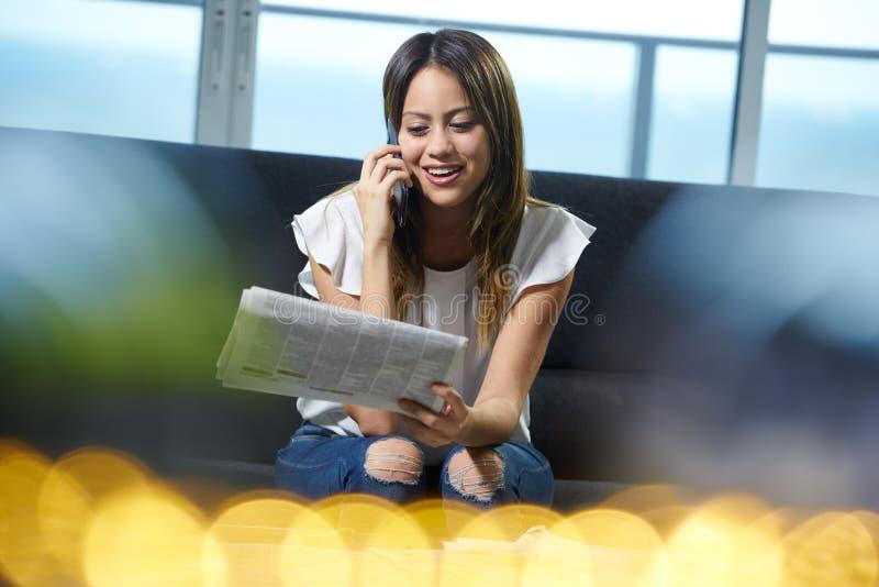 Teléfono de la mujer que pide Job Announcement On Newspaper foto de archivo