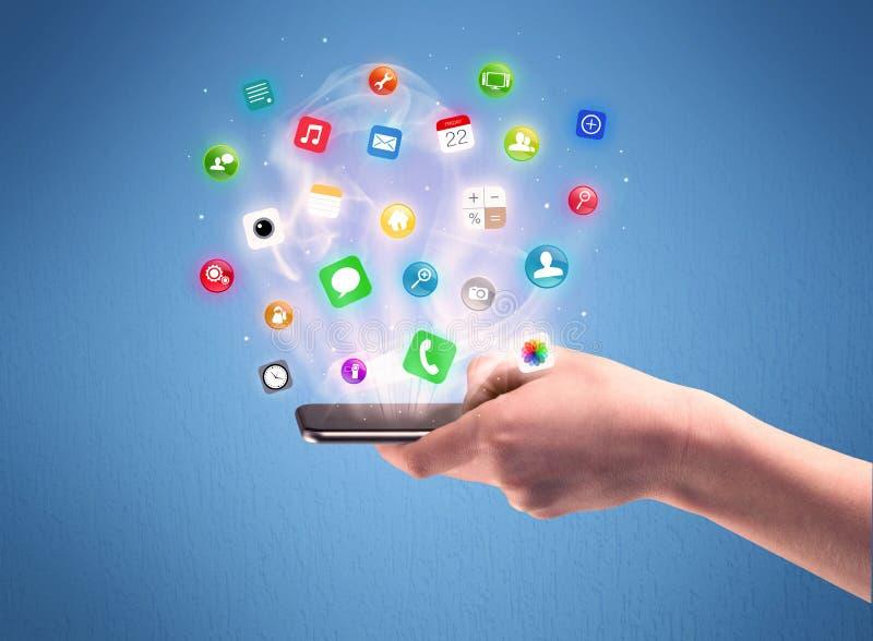 Teléfono de la tableta de la tenencia de la mano con los iconos del app fotografía de archivo