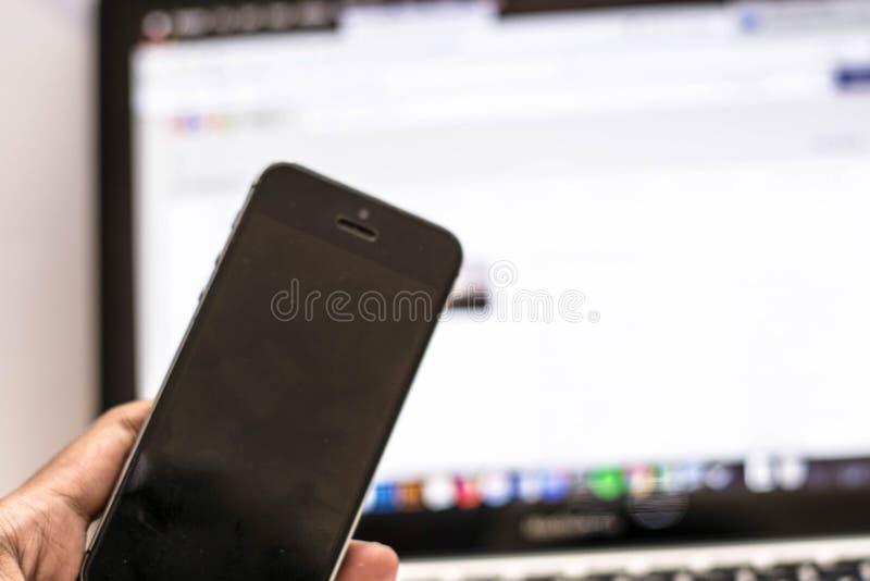 Teléfono de la tenencia de la mano delante del mercado en línea foto de archivo