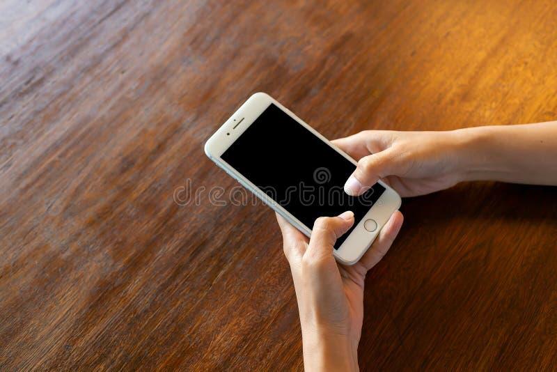 Teléfono de pantalla negro en el escritorio de madera imagen de archivo