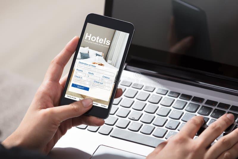 Teléfono de Person Booking Hotels Using Cell foto de archivo libre de regalías