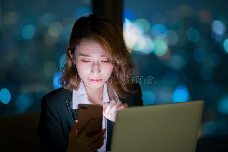 Teléfono del uso de la mujer en la noche imagen de archivo