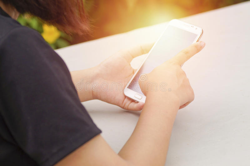 teléfono del uso de las mujeres de la mano o imagen de archivo libre de regalías