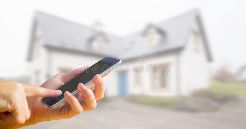 teléfono a disposición con el fondo de la casa imagenes de archivo