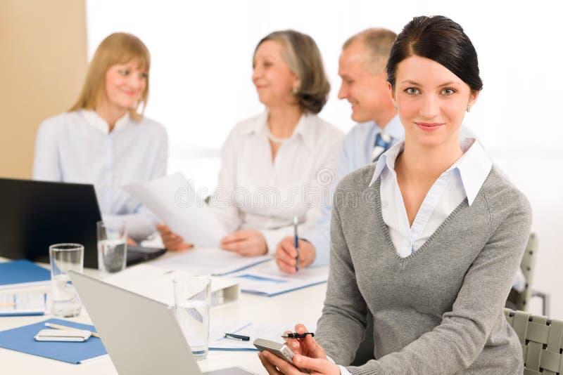 Teléfono ejecutivo joven del uso de la mujer durante la reunión foto de archivo