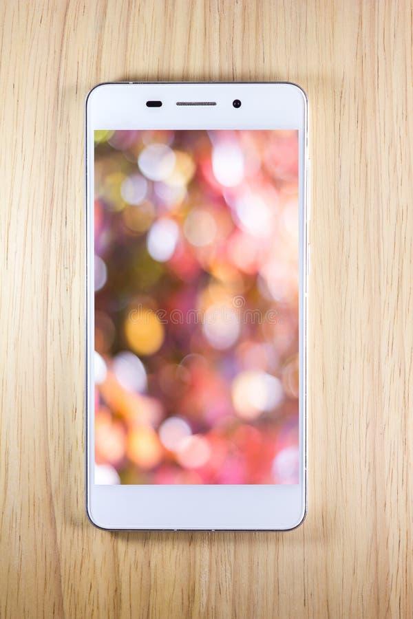 Teléfono elegante blanco con la pantalla en fondo de madera foto de archivo