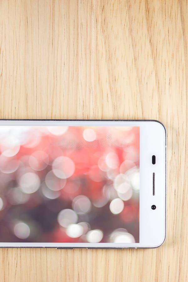 Teléfono elegante blanco con la pantalla en fondo de madera imagen de archivo libre de regalías