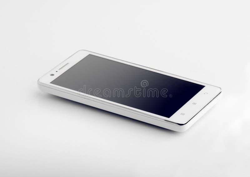 Teléfono elegante blanco en el primer superficial blanco imagen de archivo libre de regalías